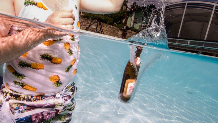 Bierflasche fällt in Wasser